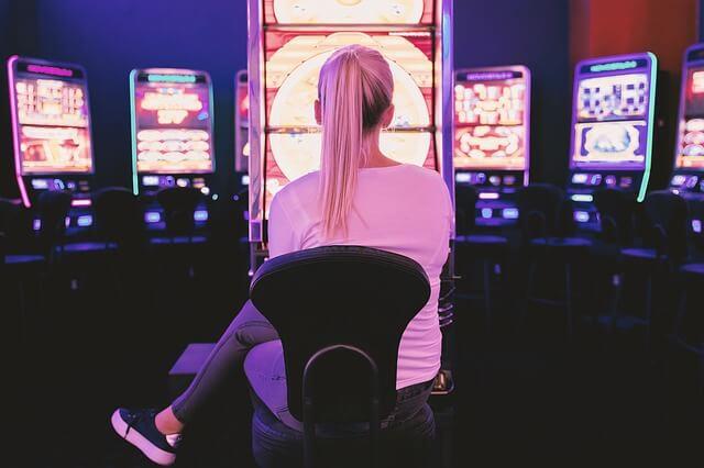Nainen istuu peliautomaattien edessä